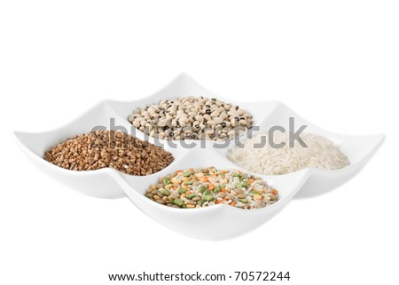 On a light plate, separately from each other, lies three kinds of popular groats and beans. A shot horizontal, focus in the middle of a shot. - stock photo