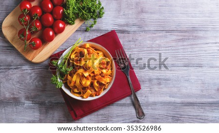 On a light wooden background in vintage style food dinner plate with Bolognese Tagliatelle pasta, cherry tomatoes on a branch, fork, napkin, towel red, green curly parsley - stock photo
