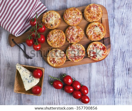 On a light wooden table background in rustic several mini-pizzas with ham and cheese, cherry tomatoes on a branch, a piece of blue cheese, top view - stock photo