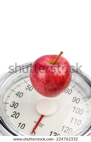 on a personal scale is an apple. symbol photo for weight loss and healthy, vitamin-rich diet. - stock photo