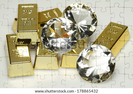 On a Puzzle Gold bars and diamonds are shown. - stock photo