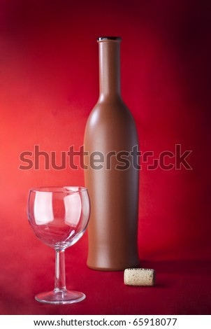 on a red background clay bottle, glass and cork - stock photo