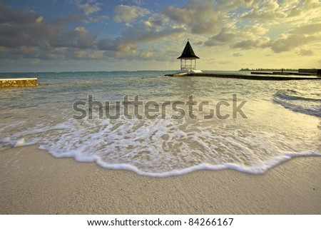 on a sandy beach early in the morning sunrise - stock photo