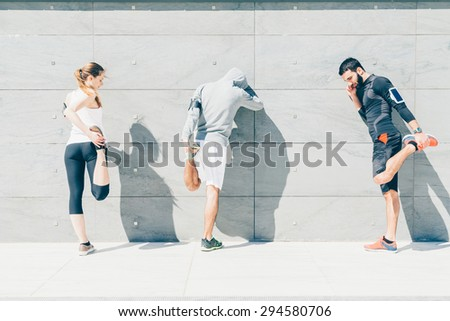 On a sunny day, a three friends in sportswear does stretching outdoors near a building  - stock photo