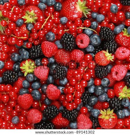 On a table are lying strawberries, bilberries, red currants, raspberries and blackberries - stock photo