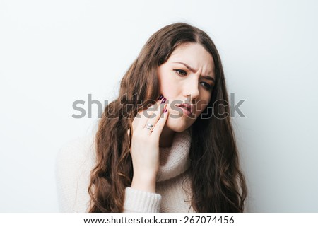 on a white background a young girl with long hair toothache - stock photo