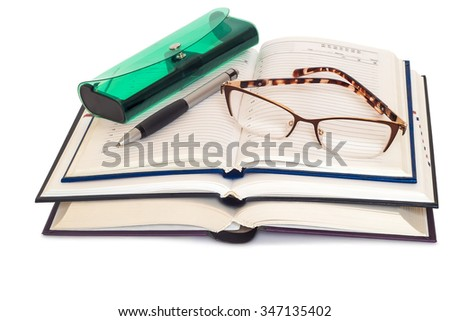 On a white background presented two books and a notebook. They are glasses, eyeglass case and pen.