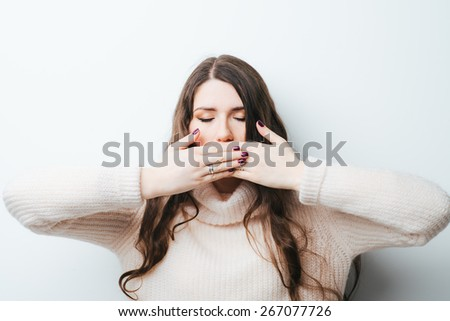 on a white background young girl with long hair covers her mouth with her hands - stock photo