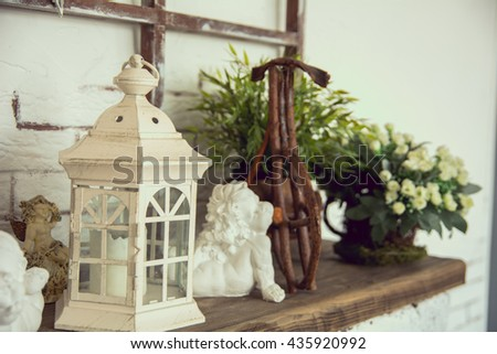 On a wooden board lamp, a ceramic angel toy bicycle and white flowers - stock photo