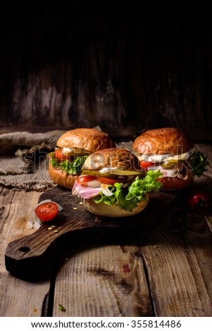On a wooden board three home burger with pork and vegetables .