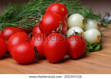 On a wooden chopping board are natural tomato, onion and dill