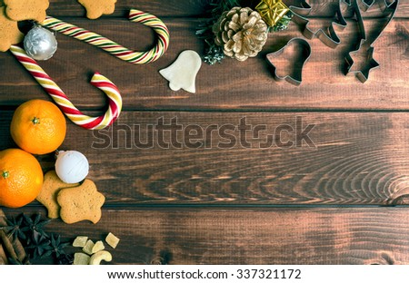 On a wooden desk background Christmas composition - candy cane, dough figurines, Christmas-tree branch Christmas balls, raisins, nuts, cinnamon sticks, cookies, star anise, mandarins; bump - stock photo