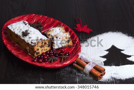 On a wooden desk background Christmas Stollen, toy Angel, a red dish with crochet pattern, powdered sugar like snow, cinnamon sticks, star anise, tree of powdered sugar