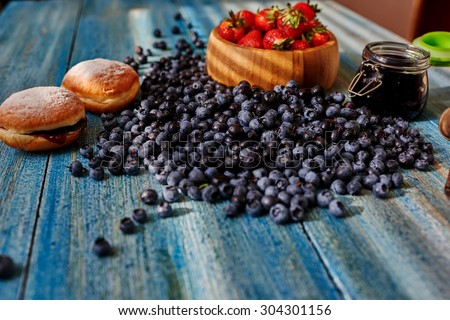 On a wooden kitchen table, laid out breakfast, two fresh muffins and fresh berries - stock photo