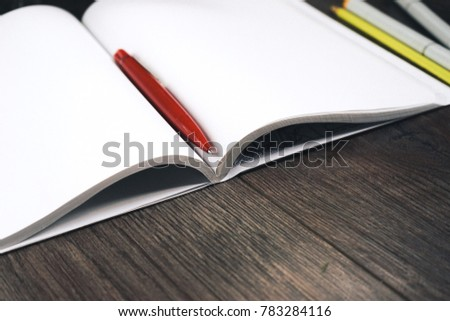 on a wooden surface is a notebook with white sheets and a pen