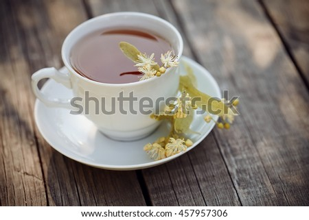 On a wooden table a white cup of tea with lime flowers.