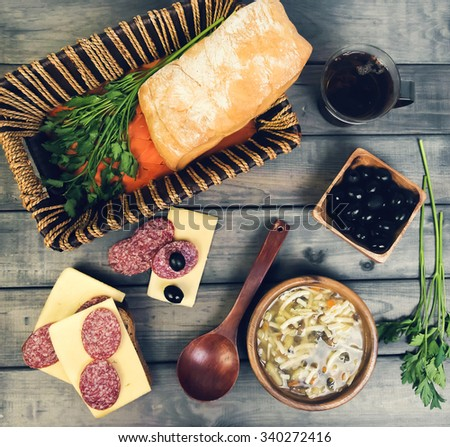 On a wooden table in the rustic lunch - soup, bread and sandwiches with sausage and cheese, olives, parsley, tea, baskets, utensils - stock photo