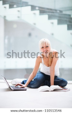 On campus - pretty female student with laptop and books working before class on her assignment/homework  (color toned image) - stock photo