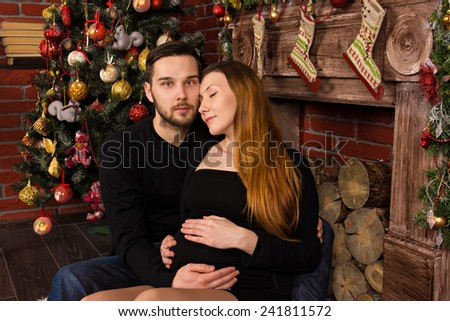 on Christmas Day, sitting by the fireplace near the Christmas tree pregnant young wife laid her head on shoulder her loved. man hugging his beloved - stock photo