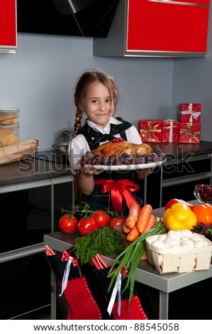 On Christmas Eve, the little girl in the kitchen by a uniformed chef serves roasted turkey on a platter with grapes. Kitchen table with fresh produce