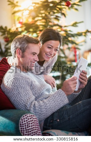 On Christmas morning, beautiful couple sitting in the living room, using a tablet, behind a decorated Christmas tree, the sun through the window give a cozy atmosphere - stock photo
