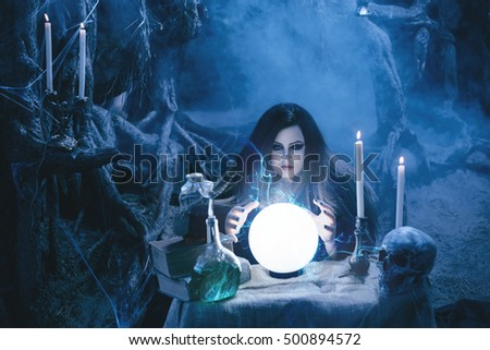 On eve of Halloween witch casts a spell, uttering terrible incantations on a glowing, crystal ball. Fabulous, spooky voodoo shack. Candles, bottles of potion. Fashionable toning. Creative color