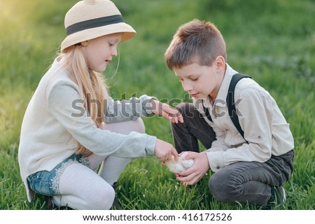 on green grass boy with blond girl in a hat plays with chicken - stock photo