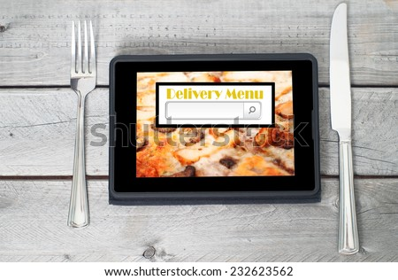 On-line and Internet food delivery concept with a digital tablet - stock photo
