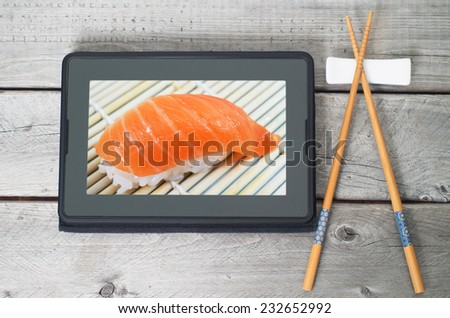 On-line and web asian food ordering concept with digital table and chopsticks - stock photo