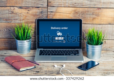 On line Delivery Order text in a laptop screen. Home interior. - stock photo