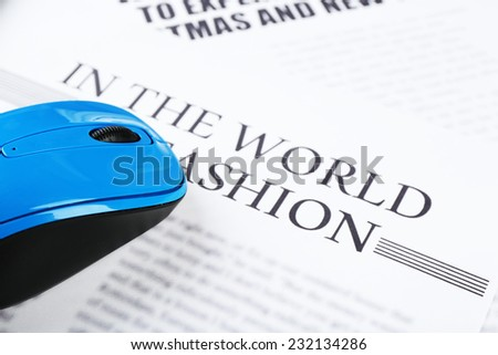 On-line news concept.Computer mouse and newspaper, close-up - stock photo