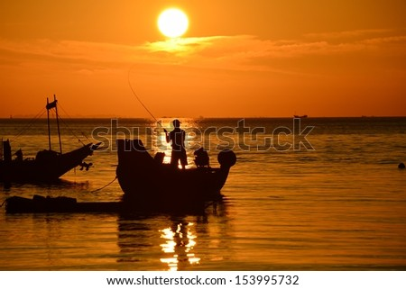 on man fishing in boat in the sea at sunrise