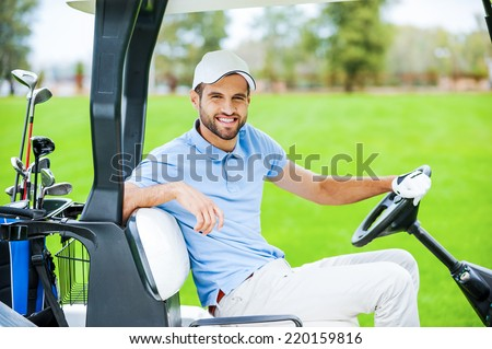 On my way to the next hole. Side view of young happy male golfer driving a golf cart and looking at camera - stock photo