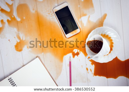 On office desk ,Coffee spilled on mobile phone (concept for working hard, clumsy or repair service) - stock photo