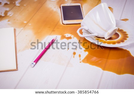 On office desk ,Coffee spilled on phone with copy space - stock photo