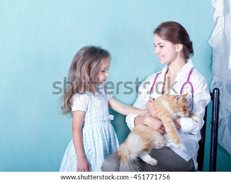 on reception at the vet.little girl stroking her cat who sits in the hands of a girl vet  - stock photo