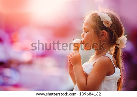 On seacoast the girl eats ice-cream at yachts background - stock photo