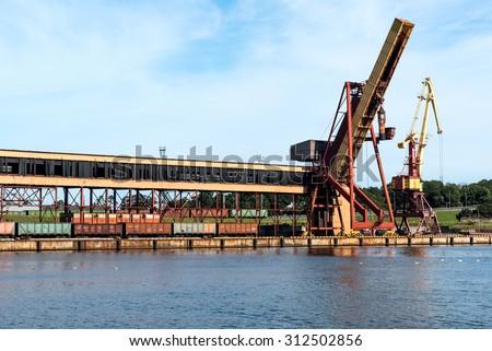 On-shore coal cargo terminal with heavy duty conveyor and a crane - stock photo