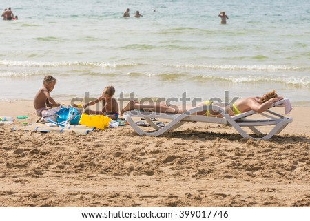 On the beach near the water with a beach chair sunbathing woman near the children playing in the sand - stock photo