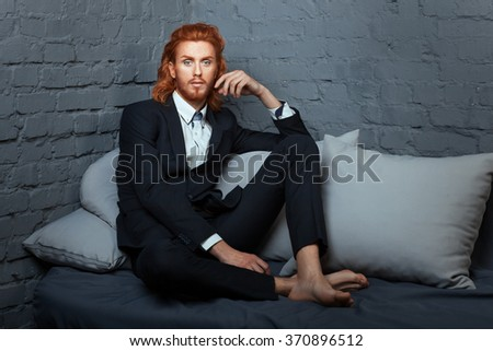 On the bed a man with freckles and red hair. He wore a stylish suit. - stock photo