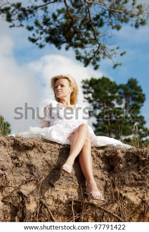 on the edge.beautiful woman in white dress sitting on the edge of a precipice