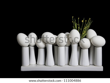 On the Edge: Eggs carefully positioned on small white pedestals with yellow flowers against black background.