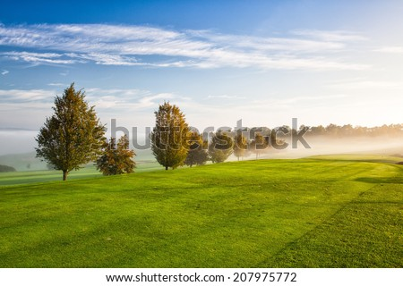 On the empty golf course in the morning mist - stock photo