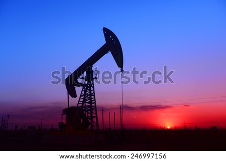 On the evening of a pumping unit is operations in oilfield, close-up  - stock photo