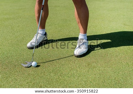 On the golf course. Golfer holding a a club and is going to hit the golf ball. - stock photo