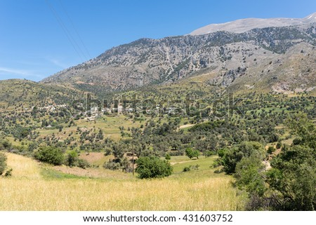 On the old road to Rethymnon in springtime. View to the mountain village Kouroutes on Crete. In the background, the Ida mountain range with the Psiloritis as the highest elevation on Crete.  - stock photo