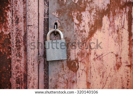 On the old wooden door, installed a rusty padlock - stock photo