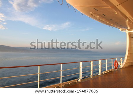 On the open deck of a cruise ship on a calm day, with the coast in the distance. - stock photo