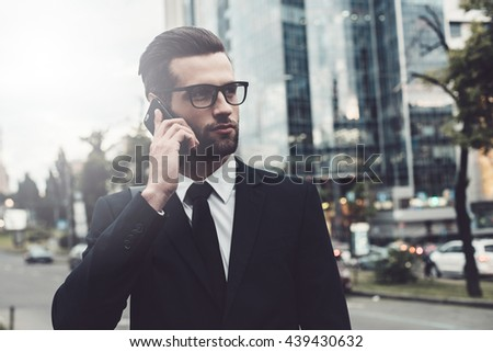 On the phone. Confident young man in full suit talking on the mobile phone and looking away while standing outdoors with cityscape in the background