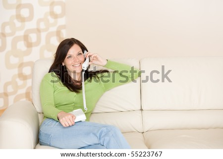 On the phone home: Smiling woman calling in living room - stock photo